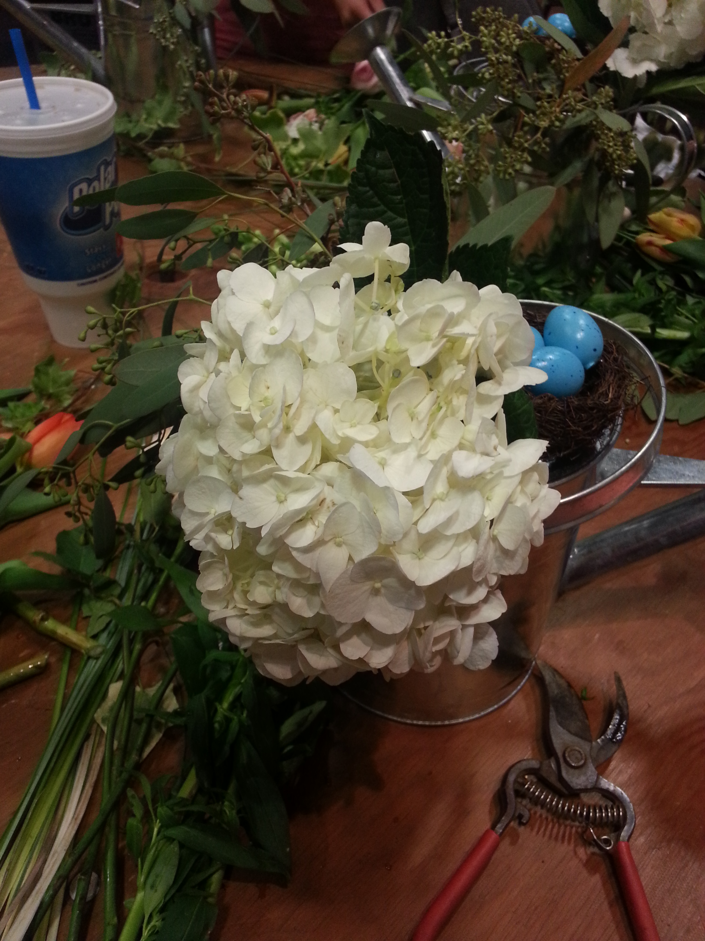 Add your hydrangea so that it rests on the top of the watering can. I ultimately add a second to give more fullness.