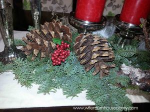 Pinecones, berries and feathers help connect the wreath and the centerpiece.